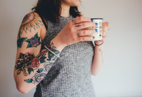 A woman in a grey tank top holds a mug and shows her many, colorful tattoos from her shoulder to her wrist.