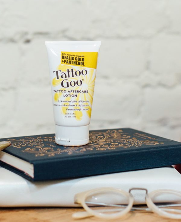 A bottle of Tattoo Goo aftercare lotion with Helix Gold and Panthenol sits atop two books, behind a pair of glasses.