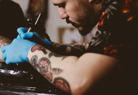 A tattoo artist wearing blue gloves, working on a tattoo on someone's arm.