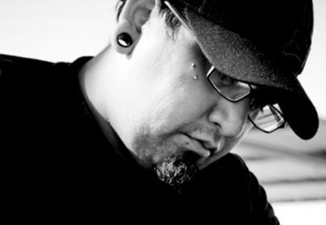 A man wearing glasses and a baseball cap looks down at something. He has a piercing in his cheek and ear gauges.