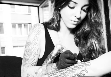 A young woman with a large arm tattoo, holds a tattoo gun and finishes a tattoo on another person's forearm.