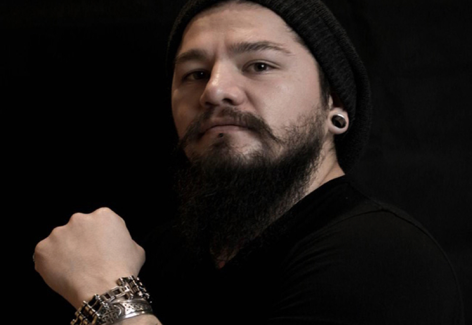 A bearded man wearing a black knit hat and black shirt has ear gauges and large metal bracelets.