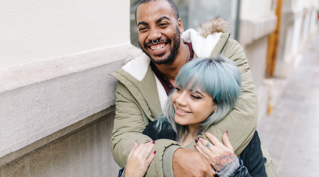 A couple smiling; the man has his arms around the woman's shoulders. Her hands, on his arms, are colorfully tattooed.