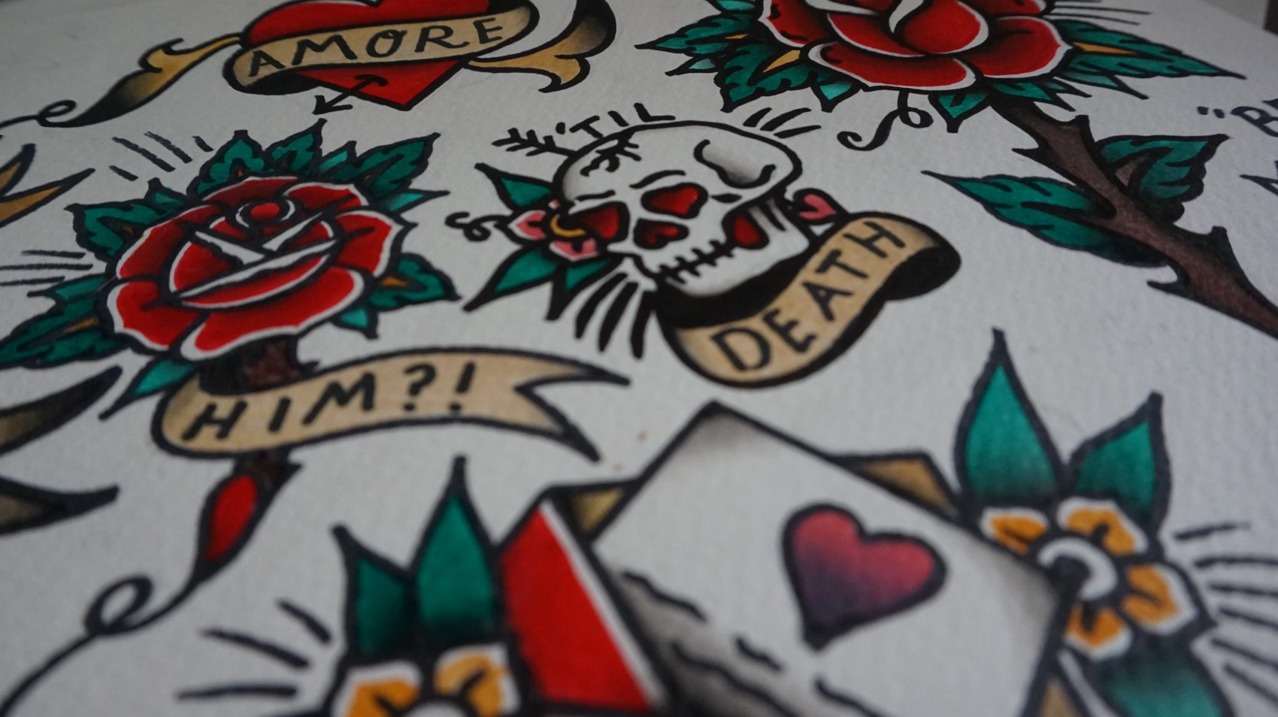 Multiple tattoo designs on white paper: a skull with red heart eyes that says til death, a heart with an arrow through it.